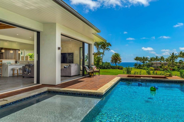 view of mansion with pool overlooking beach